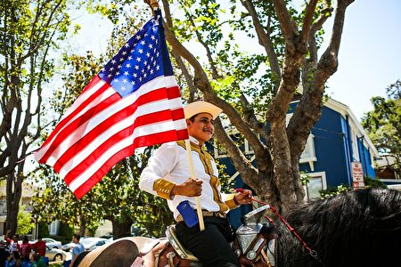 A man carries a flag as he rides a horse during the 4th of July Parade in Alameda, California on Monday, July 4, 2016. / AFP / GABRIELLE LURIE (Photo credit should read GABRIELLE LURIE/AFP/Getty Images)