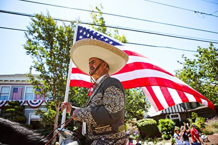 A man holds an American flag as he rides a horse during the 4th of July Parade in Alameda, California on Monday, July 4, 2016. / AFP / GABRIELLE LURIE (Photo credit should read GABRIELLE LURIE/AFP/Getty Images)