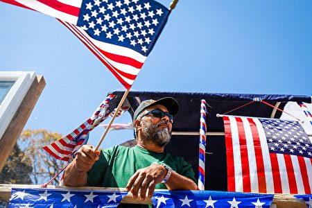 A man waves an American flag from a float during the 4th of July Parade in Alameda, California on July 4, 2016. / AFP / GABRIELLE LURIE (Photo credit should read GABRIELLE LURIE/AFP/Getty Images)