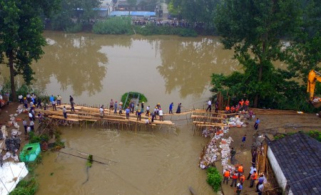 Chinese soldiers and workers try to repair a collapsed dam along the Xiangyang River in Xinji Village in Yangzhou, in east China's Jiangsu province on July 6, 2016. Heavy rain around China's Yangtze river basin has left 128 people dead and scores missing, media said on July 5, with more damage feared from a typhoon expected to land this week. / AFP / STR / China OUT (Photo credit should read STR/AFP/Getty Images)