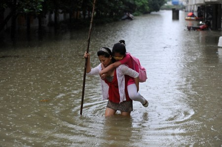This picture taken on July 5, 2016 shows a woman carrying her daughter through a flooded area in Zongyang county, in east China's Anhui province. Heavy rain around China's Yangtze river basin has left 128 people dead and scores missing, media said on July 5, with more damage feared from a typhoon expected to land this week. / AFP / STR / China OUT (Photo credit should read STR/AFP/Getty Images)