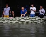 7月6日武汉居民经历暴雨袭击后,站在沙包后面一脸茫然。(Wang He/Getty Images)