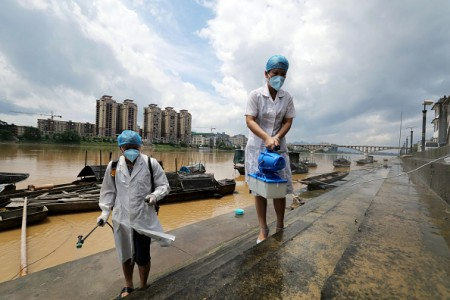This picture taken on July 6, 2016 shows epidemic prevention workers spraying disinfectant after flooding in Rongan in southern China's Guangxi Zhuang Autonomous Region. Heavy rain around China's Yangtze river basin left at least 128 people dead with scores missing, media said on July 5, with more damage feared from a typhoon expected to land this week. / AFP / STR / China OUT (Photo credit should read STR/AFP/Getty Images)