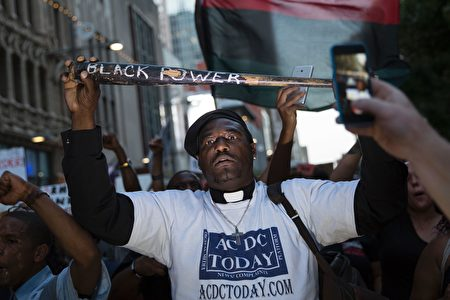 """A man holds a bat reading """"Black Power"""" during a protest in Dallas, Texas, on Thursday, July 7, 2016 to protest the deaths of Alton Sterling and Philando Castile. Black motorist Philando Castile, 32, a school cafeteria worker, was shot at close range by a Minnesota cop and seen bleeding to death in a graphic video shot by his girlfriend that went viral Thursday, the second fatal police shooting to rock America in as many days. / AFP / Laura Buckman (Photo credit should read LAURA BUCKMAN/AFP/Getty Images)"""