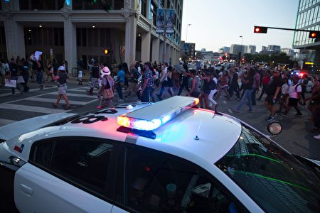 People rally in Dallas, Texas, on Thursday, July 7, 2016 to protest the deaths of Alton Sterling and Philando Castile. Black motorist Philando Castile, 32, a school cafeteria worker, was shot at close range by a Minnesota cop and seen bleeding to death in a graphic video shot by his girlfriend that went viral Thursday, the second fatal police shooting to rock America in as many days. / AFP / Laura Buckman (Photo credit should read LAURA BUCKMAN/AFP/Getty Images)