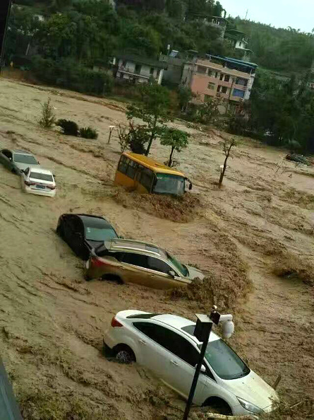 This image taken with a cameraphone shows cars and buses being washed away by floodwaters in Fuzhou, in eastern China's Fujian province on July 9, 2016. A tropical storm made landfall in China on July 9, the country's national meteorological center said, a day after Super Typhoon Nepartak lashed Taiwan with powerful winds and torrential rain. / AFP / STR / China OUT (Photo credit should read STR/AFP/Getty Images)