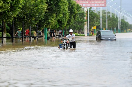 A man makes his way through a flooded street in Putian, in eastern China's Fujian province on July 9, 2016. A tropical storm made landfall in China on July 9, the country's national meteorological center said, a day after Super Typhoon Nepartak lashed Taiwan with powerful winds and torrential rain. / AFP / STR / China OUT (Photo credit should read STR/AFP/Getty Images)