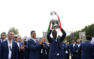 TOPSHOT - Portugal's forward Eder (C-R) raises the Euro 2016 football championship trophy next to Portugal's forward and captain Cristiano Ronaldo as players leave the team's base camp in Marcoussis on their way to the airport to fly to Portugal on July 11, 2016, a day after Portugal won the UEFA Euro 2016 football tournament. / AFP / FRANCISCO LEONG        (Photo credit should read FRANCISCO LEONG/AFP/Getty Images)