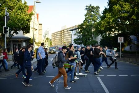 图为7月15日,德国汉诺威青年拿着手机一边玩Pokemon Go,一边通过市中心的马路。将近1200名玩家参与这项夜行穿越市中心的活动。(Alexander Koerner/Getty Images)