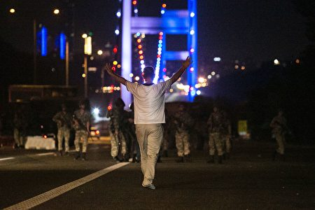 A man approaches Turkish military with his hands up at the entrance to the Bosphorus bridge in Istanbul on July 16, 2016. Turkish security forces on July 15 partially shut down the two bridges across the Bosphorus Strait in Istanbul. Turkish military forces on July 16 opened fire on crowds gathered in Istanbul following a coup attempt, causing casualties, an AFP photographer said. / AFP / Bulent KILIC AND GURCAN OZTURK (Photo credit should read BULENT KILIC,GURCAN OZTURK/AFP/Getty Images)