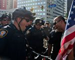 7月19日,美国共和党全国代表大会进入第2天,对立阵营的抗议者们在会场外爆发激烈冲突,上演全武行。图为一名抗议者与一名警察在抗议期间互相对峙。(ANDREW CABALLERO-REYNOLDS/AFP/Getty Images)