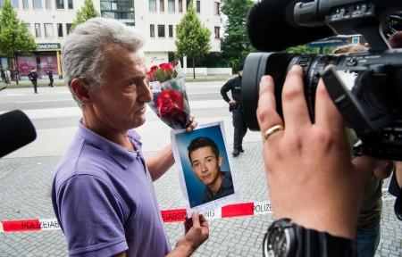7月23日,一位受难者的父亲捧着儿子的照片。( Joerg Koch/Getty Images)