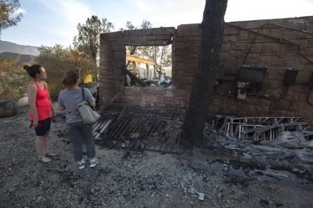 """自""""沙火""""(Sand fire)爆发以来﹐消防部门的灭火费用估计已达2800万美元。图为7月25日居民查看被烧毁的家园.。(David McNew/Getty Images)"""
