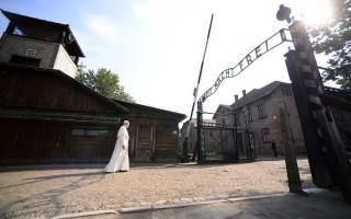 """7月29日,教宗方济各从奥斯威辛集中营大门走过,门上有臭名昭著的""""劳动带来自由""""题字。(FILIPPO MONTEFORTE/AFP/Getty Images)"""
