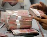 路透社6月30日引述消息来源说,中共央行将允许人民币兑美元在2016年贬值到6.8以支持经济,这将意味着今年的贬值幅度将媲美去年4.5%的跌幅。(MARK RALSTON/AFP/Getty Images)