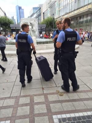 三名配枪警察将一个无主的行李箱拉走检查。(文婧/大纪元)