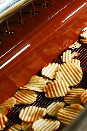 薯片巧克力的生产过程,薯片从液体巧克力瀑布帘中穿过。(ROYCE' 提供)