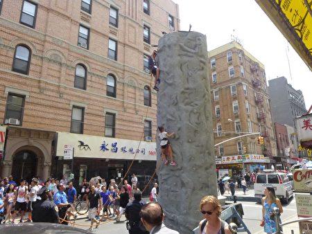 24日華埠「夏季漫遊節」,小孩子們在街上玩攀巖。