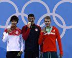 """图为""""飞鱼""""菲尔普斯(Michael Phelps)(中)和银牌得主日本选手阪井圣人(Masato Sakai)(左)及铜牌得主匈牙利泳将塔马斯.肯德瑞西(Tamas Kenderesi)在领奖台上。(Odd ANDERSEN/AFP)"""