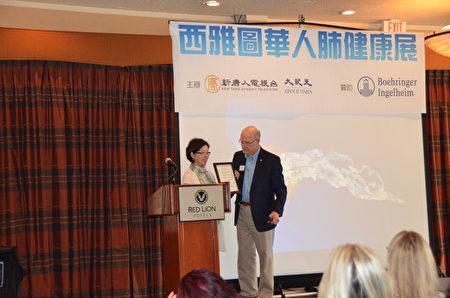 贝尔维尤市长John Stokes先生为《大纪元时报》西雅图报社颁发褒奖。(舜华/大纪元)