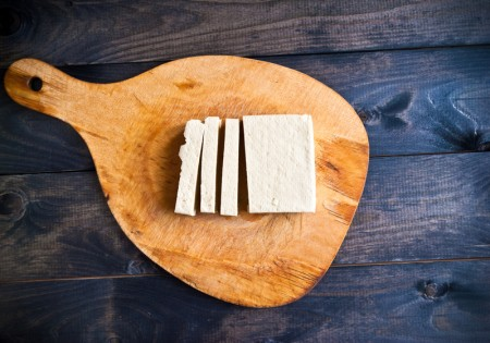 Slices of raw tofu on shabby cutting board(shutterstock)