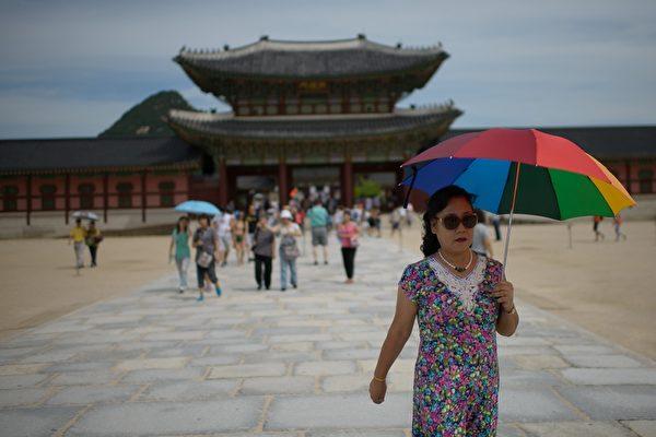"""因""""萨德""""反导系统,中共限制大陆旅客赴韩旅游。图为2014年8月27日,韩国首尔景福宫中国游客。"""