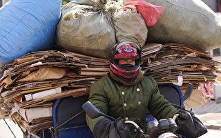 中共为了振兴东北经济拨款1.6万亿人民币给东北。图为吉林省延吉市的一名骑机车的资源回收男子。(PETER PARKS/AFP)