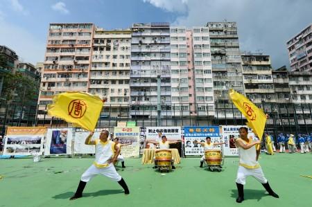 法轮功学员举办反对活摘游行,在深水埗枫树街球场开始游行到尖沙咀,途中经过闹区吸引许民众观看。图为集会中新唐人旗鼓队表演。(宋祥龙/大纪元)
