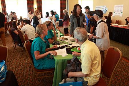 参加西雅图华人健康展的EverGreen医院经由翻译回答民众提问。(David/大纪元)
