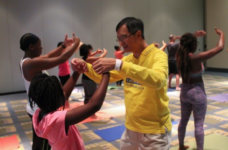 8月20日,美國一年一度的瑜伽博覽會(The Yoga Expo)在首都城市華盛頓DC沃爾特.華盛頓會議中心(Walter E. Washington Convention Center)舉行。在濟濟一堂的法輪功功法學習廳內,人們跟著台上法輪功學員范琳莎的講解,學煉法輪功功法。(於析雨/大紀元)