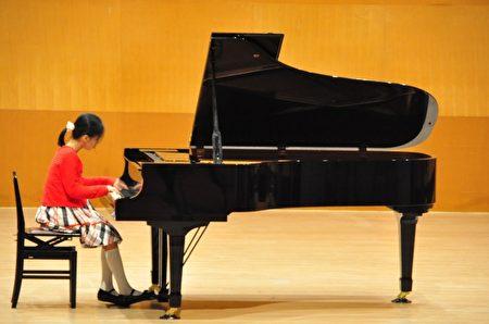 鋼琴組比賽,參賽選手聚精會神演奏,盡情發揮實力。(賴月貴/大紀元)