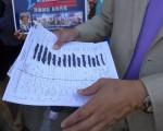 """李宗保展示被挑战的联署签名,对手指个别华人的签名是写上去,而不像老外那般龙飞凤舞,从而认定其无效。李宗保驳斥其""""吹毛求疵""""。 (蔡溶/大纪元)"""