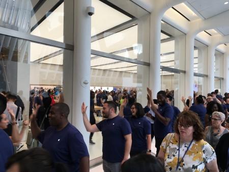 苹果员工在门口列队欢迎顾客,并和他们击掌。