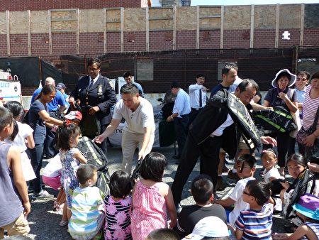 金兌錫、109分局局長哈里森、杜彼得向孩子們發放書包。