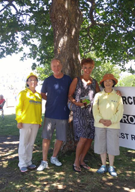 图说:8月1日,汽车之旅成员在基隆那城市公园举办真相展示。卡尔加里的法官夫妇(居中)来摊位前表达支持,并与法轮功学员合影。(大纪元图片)