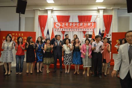 """圖: 溫哥華合家歡聯誼會會員大會晚宴上,嘉賓、理事與義工合唱""""我們都是一家人""""會歌。 (邱晨/大紀元)"""