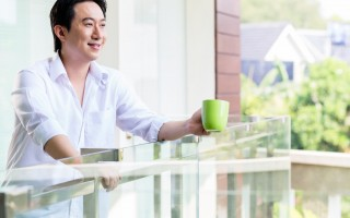 Chinese man on balcony of home with coffee in the morning