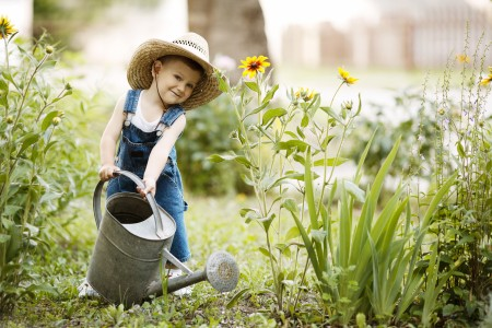 cute little boy with watering can in summer park