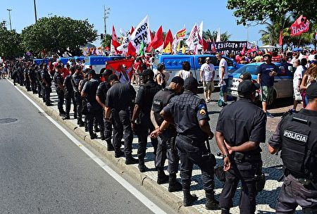 Riot police line next to a demonstration of residents of Rio de Janeiro against interim president Michel Temer, political upheaval, corruption and the cost of the Rio 2016 Olympics Games, in front of the Copacabana Palace Hotel on August 5, 2016. Thousands of Brazilians angry at political upheaval, corruption and the cost of the Rio Olympics blocked traffic in protests hours before the gala opening ceremony. Most people came to vent anger at center-right interim president Michel Temer who took power in May on the suspension of the elected leftist president, Dilma Rousseff, for an impeachment trial that her supporters claim amounts to a coup. / AFP / TASSO MARCELO (Photo credit should read TASSO MARCELO/AFP/Getty Images)