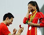 拿到铜牌的秦凯在跳水馆向刚刚获得银牌的何姿当众求婚,俩人表情令人喜悦。(Clive Rose/Getty Images)