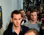 之前遭巴西警方巴西警方扣留禁止离境的美国游泳选手冈纳‧本茨(Gunnar Bentz,左)和杰克‧康格(Jack Conger,中)18日晚已获准离开巴西回美国。图为他们走出里约警察局。 (TASSO MARCELO/AFP/Getty Images)