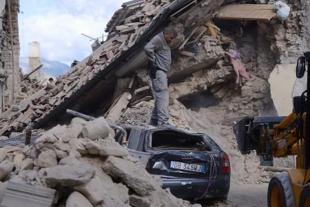 一个男人站在被损毁的车上。(FILIPPO MONTEFORTE/AFP/Getty Images)