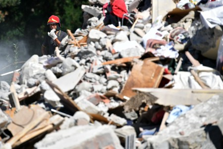 意大利中部24日发生里氏6.2强震,导致多座古城小镇严重受损。图为重灾区阿马特里切镇,救难人员在现场搜救。 (Photo by Carl Court/Getty Images)