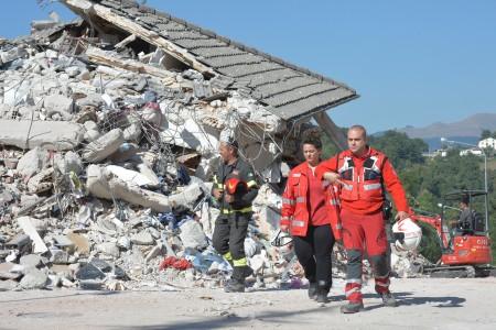 意大利中部24日发生里氏6.2强震,导致多座古城小镇严重受损。图为重灾区阿马特里切镇,在现场搜救的原救难人员。 (ANDREAS SOLARO/AFP/Getty Images)