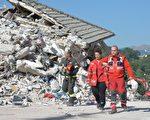 意大利中部24日发生里氏6.2强震,导致多座古城小镇严重受损。图为重灾区阿马特里切镇,在现场搜救的救难人员。 (ANDREAS SOLARO/AFP/Getty Images)