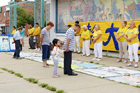 2016年7月30日,來自中部十個州的法輪功學員匯集在芝加哥中國城舉行盛大的遊行。圖為華人民眾閱讀法輪功煉功點的真相展板。(陳傑傑/大紀元)
