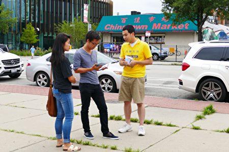 2016年7月30日,來自中部十個州的法輪功學員匯集在芝加哥中國城舉行盛大的遊行。圖為華人閱讀法輪功傳單。(陳傑傑/大紀元)