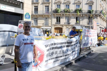 負責產品推廣的主管Pascal Gérome先生為法輪功反迫害簽名支持。(金湖/大紀元)