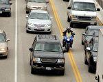 摩托车在车道间穿行。(ROBYN BECK/AFP/Getty Images)