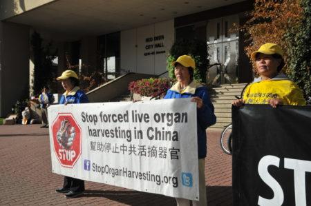 汽车之旅志愿者在红鹿市市政厅前和平抗议中共强摘器官,呼吁制止迫害法轮功。(黄钟乐/大纪元)